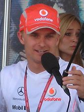 Head and shoulders of a man in his twenties as he speaks into a microphone. He is wearing a bright red, Vodafone-branded baseball cap which almost obscures his pale blond hair, and a white T-shirt which bears the Mercedes-Benz, Vodafone and Mobil 1 logos.