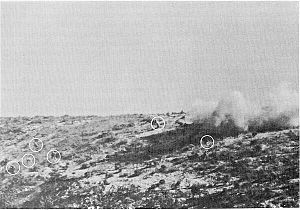 Men on a hill surrounded by explosions