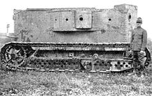 An early armoured vehicle: the rectangular body is made of riveted plates and has a number of empty gun ports. It is carried on full-length caterpillar tracks.