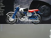 A pristine-looking 1960's-era single-cyclinder motorcycle with a blue frame and bright red seat, and a Honda wing logo on the gas tank.