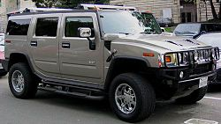 2003 Hummer H2 SUV, accessorized with roof rack, running lights, and step rails