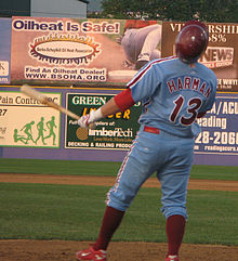 "A man in a light-blue baseball uniform with maroon trim reading ""Harman"" and ""13"" on the back; he is holding a baseball bat in his left had and wearing a maroon baseball helmet atop his head"
