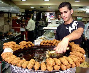 Falafel - A Palestinian man from Ramallah using an aleb falafel while frying falafel