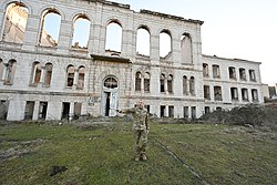 Ilham Aliyev in front of the ruined Shusha Realni School.jpg