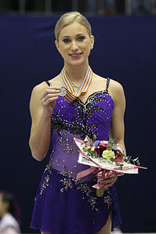 A woman in a blue dress smiles as she holds a medal and bouquet of flowers.