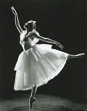 Black-and-white photograph of a female ballet dancer in a white dress, standing en point with her arms mirroring the position of her legs.