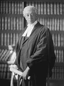 man in his early 50s wearing a lawyers' wig and gown, standing in front of a book shelf