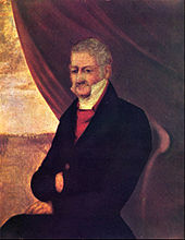Painted half-length portrait depicting a gray-haired man with a thin face dressed in a plain black coat over a red vest and high-collared white shirt and sitting in front of a half-opened drape revealing an avenue with a building in the distance