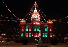 Building with strings of colored lights running from top of cupola to sides of square
