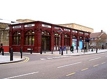 "Single storey red glazed terracotta station building with tall arched windows. Glass shaded lamps project from the façade on ornate brackets and the words ""Kilburn Park"", ""Entrance"", ""Exit"" and ""Underground"" are displayed in black on a white moulded tile band above the window arches."