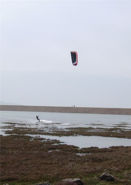 One of several kite surfers in the lee of Hurst Spit with the Isle of Wight just visible behind.