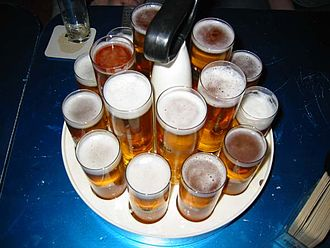 "Beer in Germany - A Kranz (wreath) of fresh Kölsch beer that is typically carried by a server (""Köbes""), containing traditional Stange glasses and, in the center, larger modern glasses"