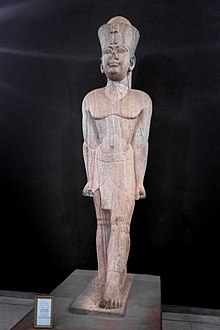 Large light-brown statue of a man striding, wearing the double crown of Ancient Egypt.