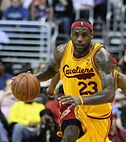 Black man dribbling a basketball with a gold and maroon basketball jersey that says Cavaliers in maroon cursive lettering across the chest. He is wearing a headband with an NBA logo.