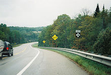 A roadway curving down a slight incline and around a bend. On the side of the road are a series of sign posts with the M-28 reassurance marker, a yellow diamond with arrows indicating the traffic directions and a yellow diamond with an arrow warning of the curve in the road.