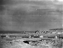 A black and white photograph of a desert landscape; in the mid distance are several huts