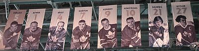 We are looking up at the ceiling of an arena where there are nine banners hanging. On each banner is the picture of a hockey player in a Toronto Maple Leaf uniform. Above each player's photo is a number and the player's name