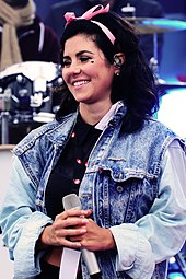A young brunette woman, standing in front of a drumkit, holding a microphone and smiling. She is wearing a denim jacket, has a heart-shaped mark on her left cheek and has a pink bow in her hair.