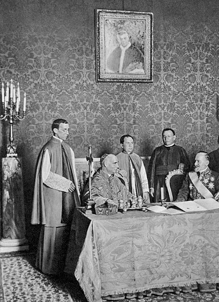 Monsignor Eugenio Pacelli at left and Cardinal Secretary Rafael Merry del Val at the signing ceremony of the Serbian concordat during the pontificate of Pius X, dated 24 June 1914 MarrydelValpacelli.jpg