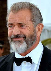 A photograph of Mel Gibson, sporting a beard and wearing a suit with matching bow tie while focused in another angle, smiling.