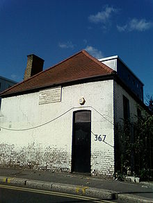 Photograph of a plain white brick building with a red roof and black door