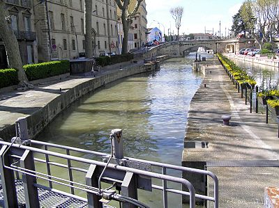 "The Canal de la Robine in 2003. (Taken from the ""Passerelle entre Deux Villes"" pedestrian bridge, facing northwest, away from the heart of the city.)"