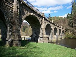 A handsome bridge, built from multiple semi-circular arches of buff sandstone spans the river in picturesque surroundings. Four of the piers are in the water and the helical courses of stone attest to its oblique construction. Atop the parapet is a cast iron railing.