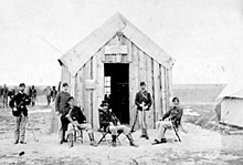 Black and white photo of a group of men in uniforms in front of a wooden building