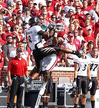 2008 Oklahoma Sooners football team - OU's Ryan Broyles and Cincinnati's Brandon Underwood both go up to catch a pass from QB Sam Bradford.