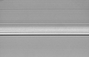 Density wave theory - Spiral density waves in Saturn's A Ring induced by resonances with nearby moons.