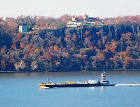 Panoramic view looking west from London Terrace. A barge on the Hudson River and the Hudson Palisades beyond, with the Englewood Cliffs campus of Saint Peter's University on the top of the Palisades