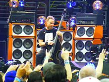 A male bassist, Jeff Ament, playing upright bass in a concert. He is seated in front of several large, tall speaker cabinets.