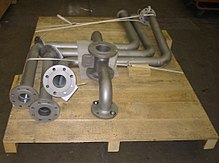 Several heavy pieces of bent pipe with flange connections, strapped down to a wooden pallet