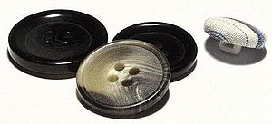 Button - Three plastic sew-through buttons (left) and one shank, fabric-covered button (right)