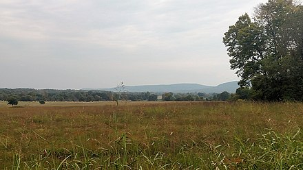 The Lower Boston Mountains (background) rise from the flat, grassy Springfield Plateau at Prairie Grove Battlefield State Park in Prairie Grove Prairie Grove Battlefield State Park 006.jpg