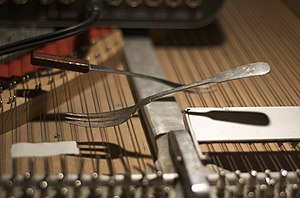 Prepared piano - Andrea Neumann's preparations, where pieces of cutlery are placed between piano strings