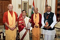 A color photo of the President flanked by Hare Krishna followers in robes, holding a copy of the Bhagavad Gita in Russian.