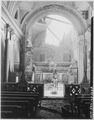 Private Paul Oglesby, 30th Infantry, standing in reverence before an altar in a damaged Catholic Church. Note, pews... - NARA - 531181.tif