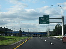 "Ground-level view of a freeway; a large, green sign marked with ""Exit 7"" is posted directly overhead. Two large bridges are visible in the distance."