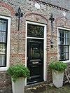 foto van Huis met trapgevel. Sierankers. Gele baksteen met donkerrode lagen en bogen. Muizetand, toppilaster. Benedenstuk gepleisterd