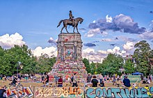 A bronze statue of a man riding a horse on a tall pedestal that is covered in colorful graffiti.