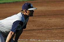 A man wearing a sleeveless gray baseball jersey with blue undershirt and a blue cap crouching