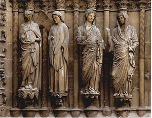 Four carved figures are set between columns and are mounted against the wide angled jamb of a medieval door. The figures are paired to illustrate two stories. To the left, a smiling angel approaches Mary who raises her hand. in the right groupt, Mary approaches her elderly cousin Elizabeth who turns her eyes to heaven. The style of the two groups is entirely different, the first being simpler and more elegant, the second having very elaborate drapery and realistic detail.