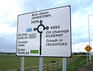 Road signs in Ireland - Black-on-white regional road sign in Irish and English, showing Guildford Rules patching for the N75 and the M8