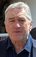 Photo of Robert De Niro--a white man of 70 years with white hair, wide nose, square face and small eyes, wearing a dark blue shirt--at the 2016 Cannes Film Festival.