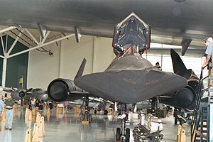 An SR-71 Blackbird under the wing of the Spruc...