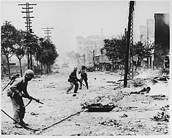 U.S. Marines engaged in urban warfare during the battle for Seoul in late September 1950; the American soldiers are carrying M1 Garand semi-automatic rifles and Browning Automatics. On the street are Korean civilians who died in the battle. In the distance are M4 Sherman tanks.