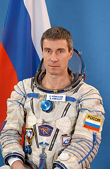 Krikalev posing in a space suit in front of the Russian flag