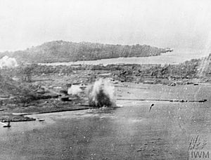 Black and white aerial photo of shoreline with smoke rising from buildings in the centre of the image