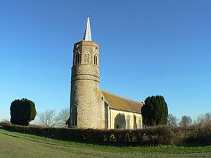 A flint church seen from the southwest, having a tall round tower with an octagonal bell stage and a lead spirelet.  The body of the church stretches to the right.